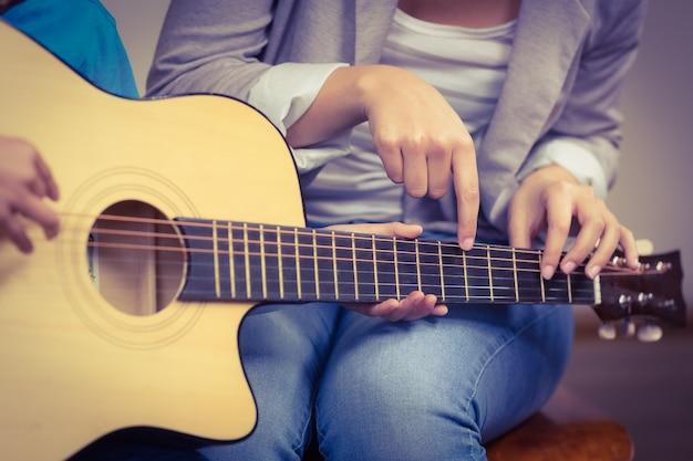 Nauczyciel udzielający lekcji gry na gitarze uczniowi