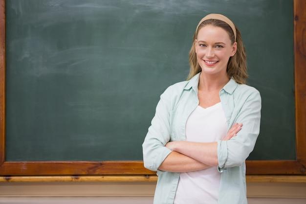 Nauczyciel uśmiecha się do kamery z rękami skrzyżowanymi