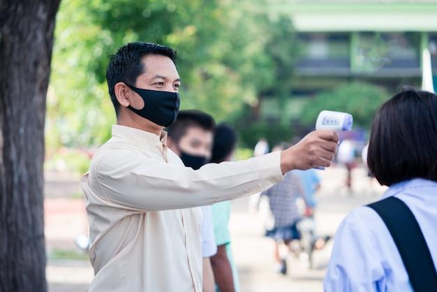 Nauczyciel używający termometru do badania przesiewowego temperatury w szkole w celu wykrycia wirusa covid-19 lub koronawirusa.