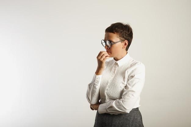 Nauczyciel w konserwatywnym biało-szarym stroju i okrągłych czarnych okularach głęboko zamyślony na białym tle