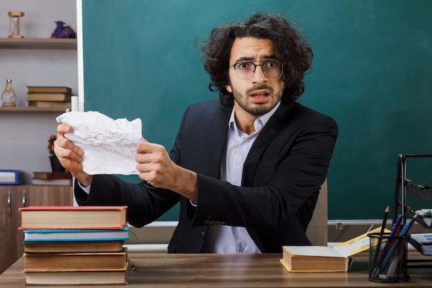 Nauczyciel w okularach trzymający miażdżący papier, siedzący przy stole ze szkolnymi narzędziami w klasie