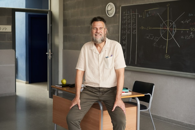 Nauczyciel w średnim wieku, brodaty mężczyzna patrzący na kamerę w klasie, szczęśliwy i zaangażowany nauczyciel