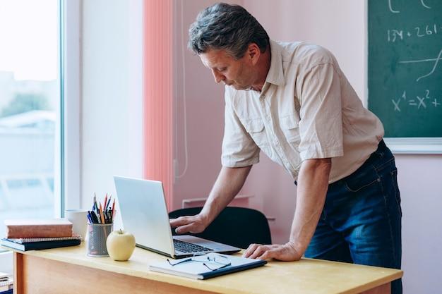 Nauczyciel w średnim wieku pochylił się nad laptopem i pisał na maszynie.