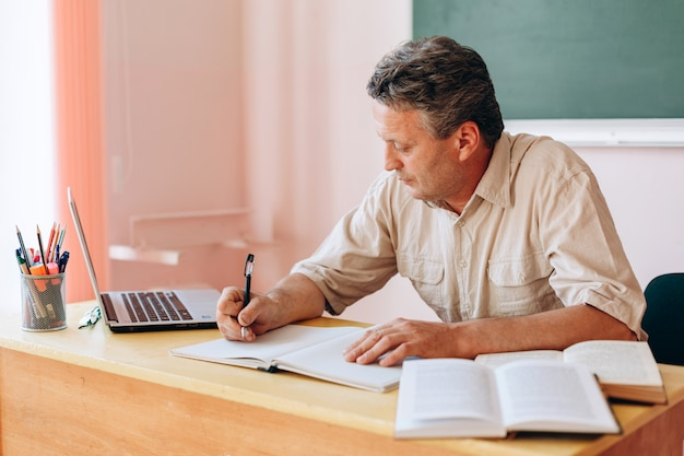 Nauczyciel w średnim wieku siedzi przy stole i pisze.
