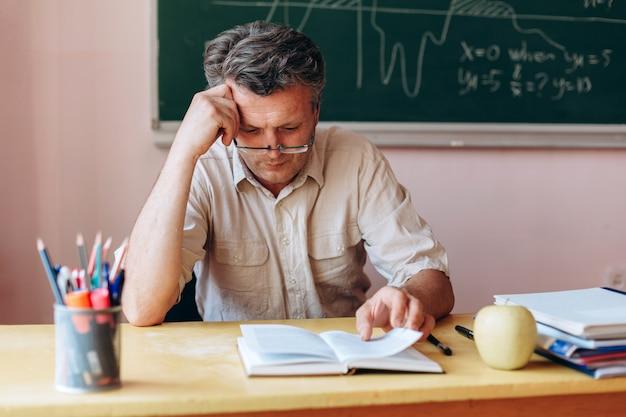 Nauczyciel w średnim wieku w okularach uważnie czytający podręcznik w klasie.
