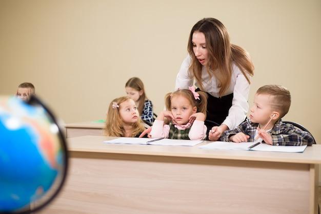 Nauczyciel w szkole podstawowej pomagający dziewczynie pisać przy biurku.