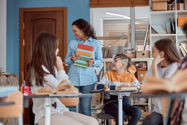 Nauczyciel w szkole podstawowej stoi w klasie. nauczycielka rozpocznie lekcję, gdy uczennice siedzą przy ławkach.
