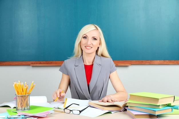 Nauczyciel w szkole siedzi przy stole na tablicy