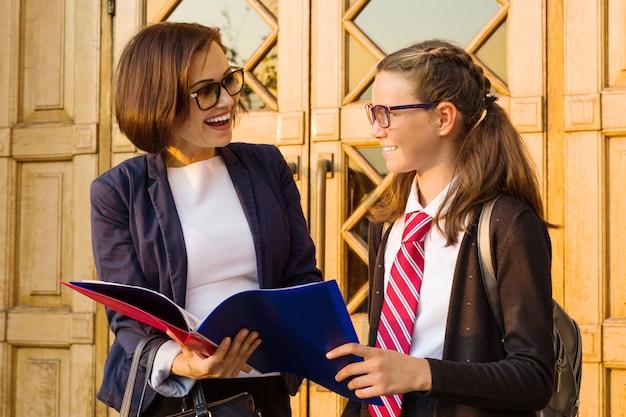 Nauczyciel w szkole średniej mówi dziewczyna student w pobliżu drzwi szkoły.