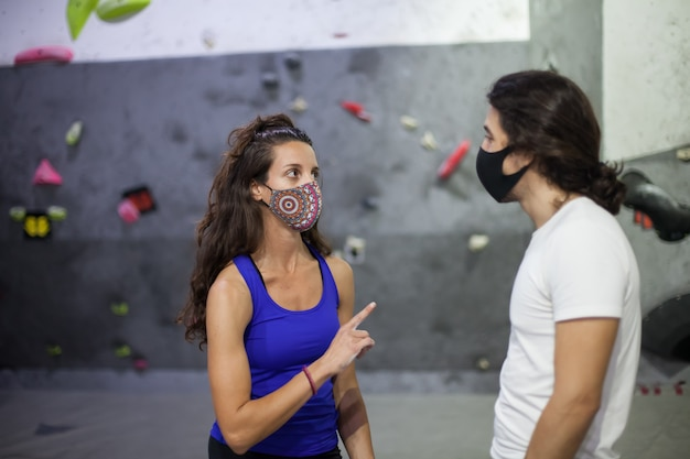Nauczyciel wspinaczki i uczeń w masce na stromej skalnej ścianie w pomieszczeniu