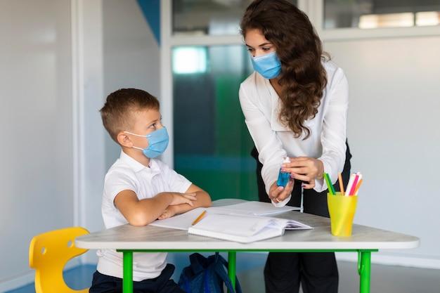 Nauczyciel wyjaśnia uczniowi znaczenie dezynfekcji