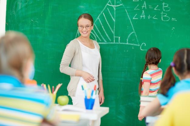 Nauczyciel wyjaśniając na tablicy