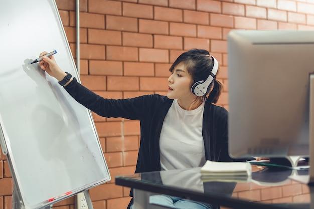 Nauczyciel z azji wyjaśnia ćwiczenia na tablicy uczniom uczącym się online.