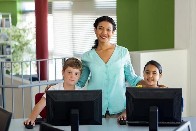 Nauczyciel z dziećmi w klasie komputerowej