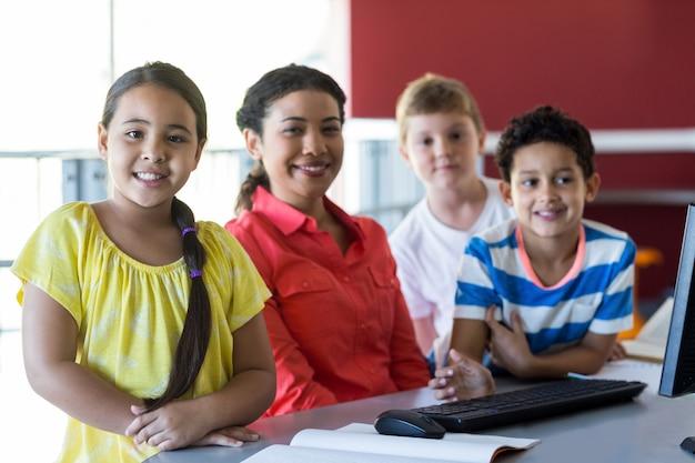 Nauczyciel z dziećmi w sali komputerowej