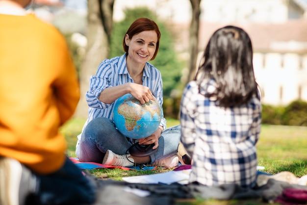 Nauczyciel z małymi dziećmi siedzącymi na świeżym powietrzu w parku miejskim, uczący się koncepcji edukacji grupowej.