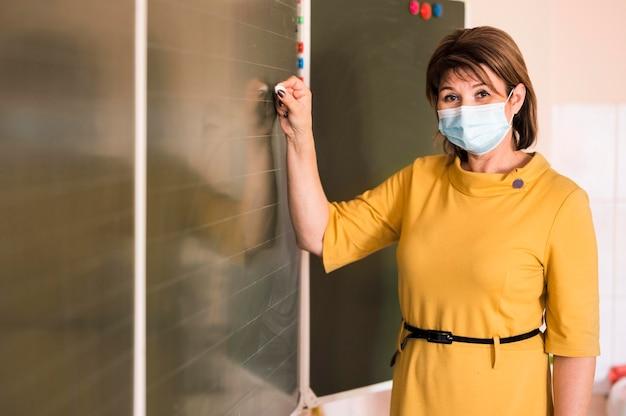 Nauczyciel z maską pisania na tablicy