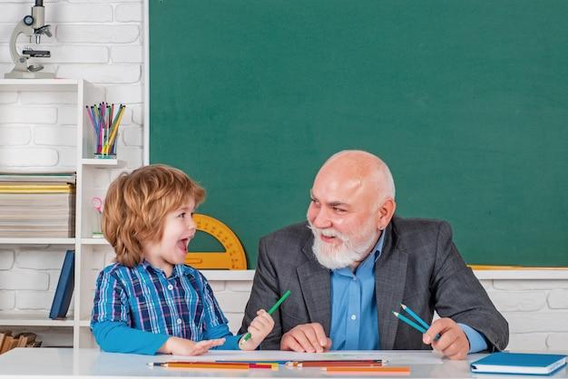 Nauczyciel z męskim uczniem szkoły podstawowej z koncepcją edukacji naukowej problem