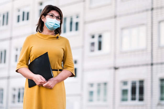 Nauczyciel z niskim kątem z maską na zewnątrz