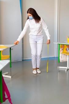 Nauczyciel z przodu mierzący odległość między biurkami