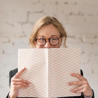 Nauczyciel z przodu zakrywający twarz książką