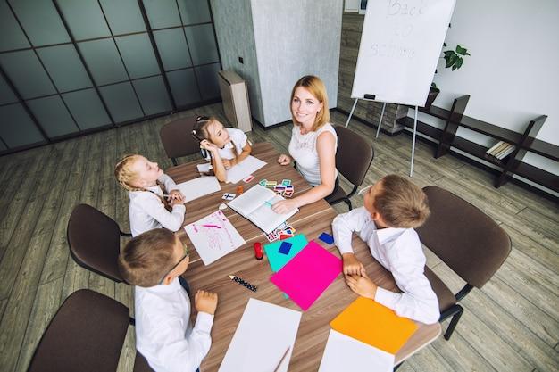 Nauczyciel z uczniami w klasie do prowadzenia nauki książki razem zabawne i pouczające