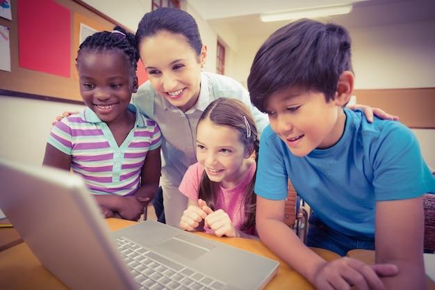 Nauczyciel za pomocą laptopa z uczniami