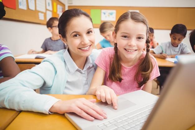 Nauczyciel za pomocą laptopa z uczniem