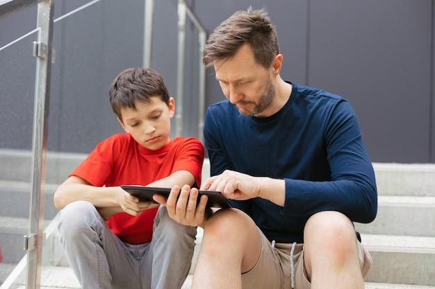 Nauczyciel zaręcza się z chłopcem na schodach za pomocą urządzenia mobilnego - tabletu. koncepcja edukacji pozaformalnej w stylu życia miejskiego