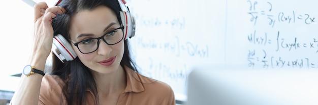 Nauczyciel ze słuchawkami na głowie patrzący na ekran laptopa