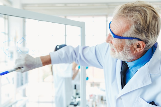 Nauczycieli nauk chemicznych mężczyzna pracuje z przejrzystymi szklanych deskę substancjami chemicznymi w lab