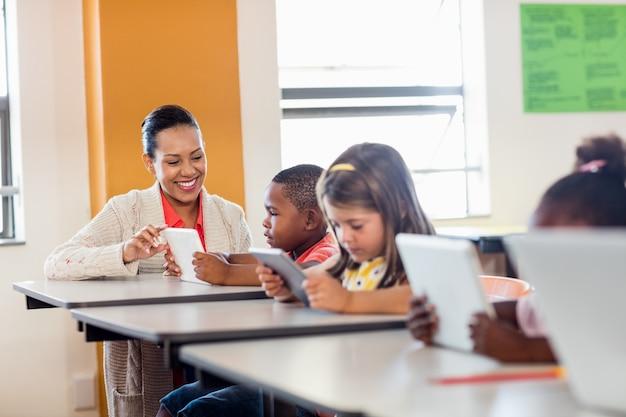 Nauczycielka daje lekcje swoim uczniom za pomocą cyfrowych tabletów