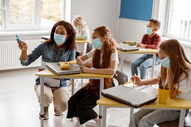 Nauczycielka kuca przy biurku dziewczyny