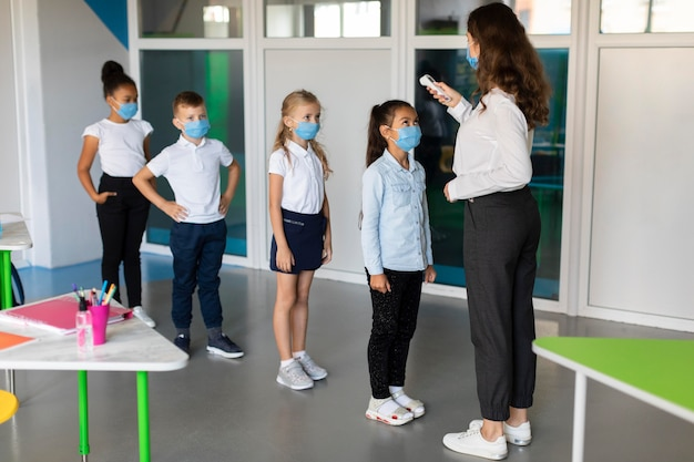 Nauczycielka mierzy temperaturę swoich uczniów