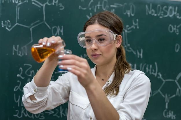 Nauczycielka mieszająca wielokolorowe płyny chemiczne podczas lekcji chemii. naukowy