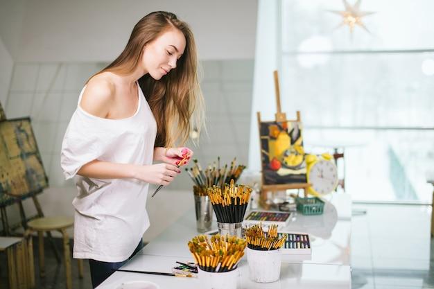 Nauczycielka naturalnego piękna malarz w pracowni przygotowującej się do zajęć plastycznych
