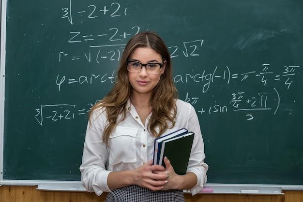 Nauczycielka pisała na tablicy wzory matematyczne i wyjaśniała lekcję. szkoła