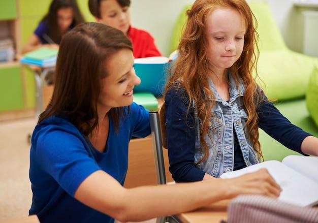 Nauczycielka pomaga swojej uczennicy w odrabianiu prac domowych