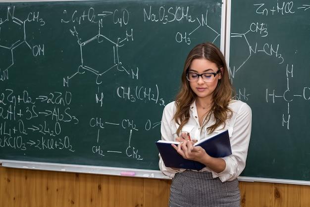 Nauczycielka przedmiotów ścisłych w okularach wyjaśnia lekcje chemii w szkole. edukacja