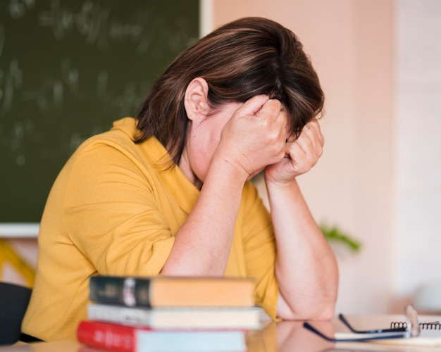 Nauczycielka przy biurku zmęczona