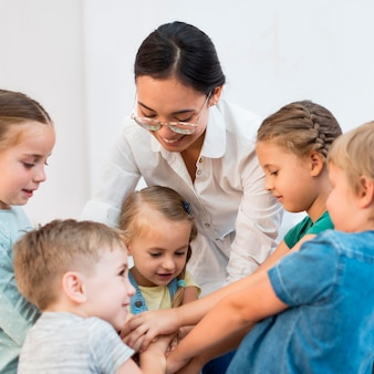 Nauczycielka składa ręce razem z uczniami