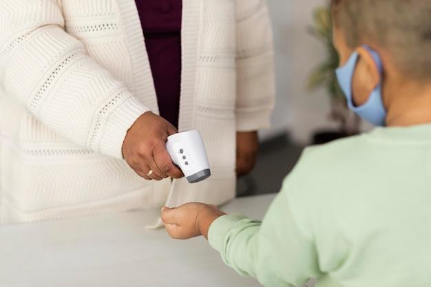 Nauczycielka sprawdzająca temperaturę każdego ucznia