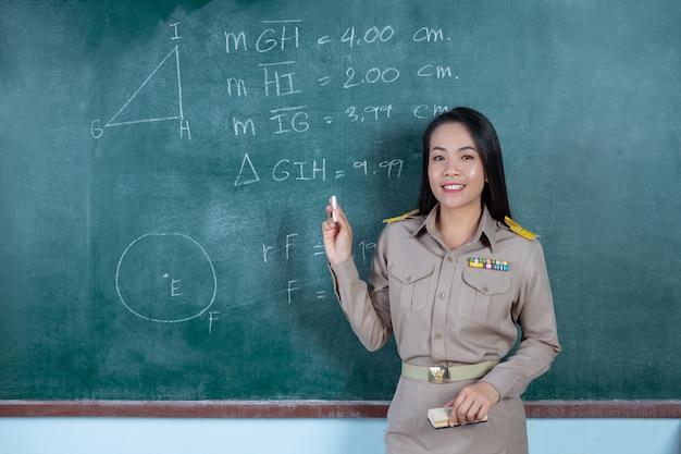 Nauczycielka tajskiego w oficjalnym stroju nauczająca przed tablicą