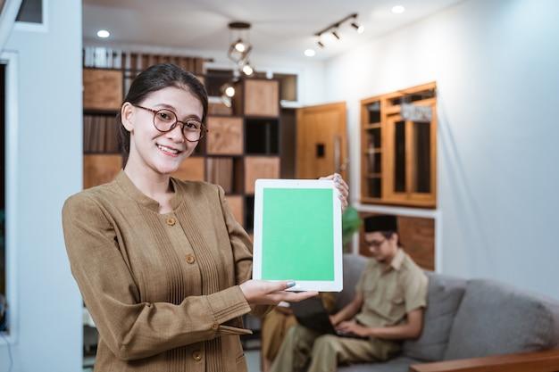 Nauczycielka w mundurze urzędnika państwowego w okularach uśmiecha się, pokazując cyfrowy tablet z...