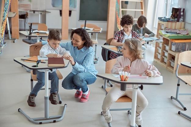 Nauczycielka wyjaśnia zasady gramatyki małego ucznia