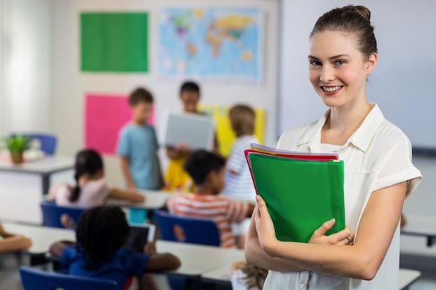 Nauczycielka z kartotekami stoi w sala lekcyjnej