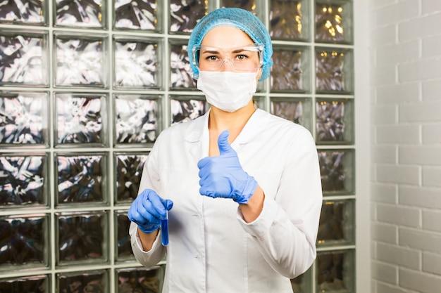 Nauka, chemia, biologia, medycyna, koncepcja ludzi - młoda kobieta naukowiec trzyma probówkę z próbkowaniem i testem lub badaniami w laboratorium klinicznym
