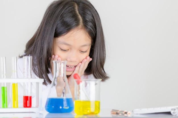 Nauka dla dzieci, szczęśliwa mała dziewczynka bawić się robić chemicznym eksperymentom w laboratorium