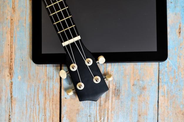 Nauka gry na gitarze hawajskiej online. podstrunnica ukulele na drewnianym stole obok ekranu tabletu