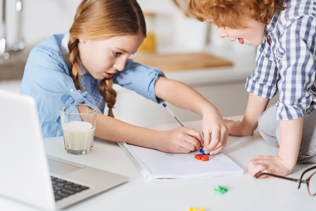 Nauka i sztuka. genialna ciekawa ładna dziewczyna rysująca obliczenia matematyczne za pomocą specjalnych kolorowych plastikowych figurek, próbująca wyjaśnić swojemu młodszemu bratu podstawowe zasady obliczania